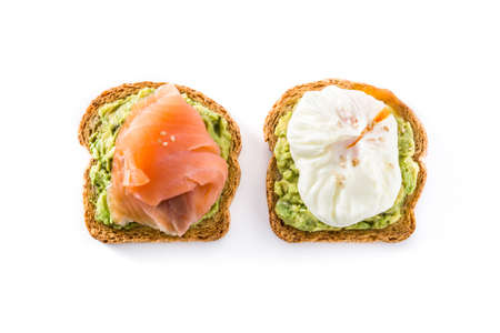 Toasted breads with avocado, poached eggs and salmon isolated on white background. Top view Stock Photo