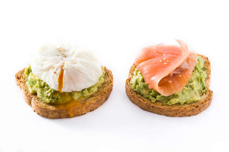 Toasted breads with avocado, poached eggs and salmon isolated on white background.