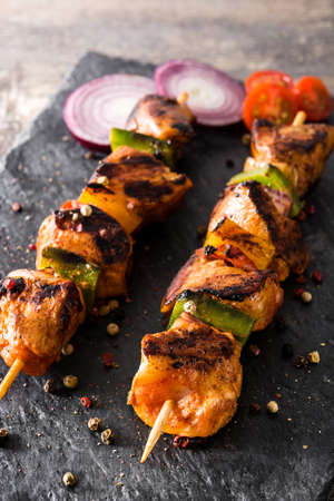 Chicken shish kebab with vegetables on wooden table