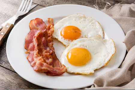 Fried eggs and bacon for breakfast on wooden table.