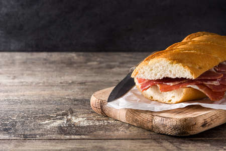 Spanish ham sandwich on wooden table.Copyspace