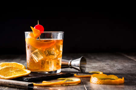 Old fashioned cocktail with orange and cherry on wooden table. Copyspace Фото со стока