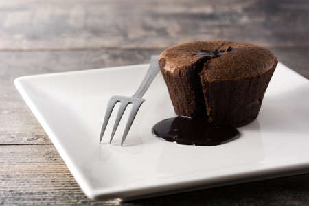 Coulant chocolate cake on wooden table. Copyspace