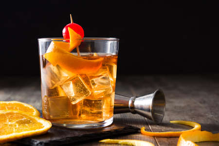 Old fashioned cocktail with orange and cherry on wooden table. Copyspace 免版税图像