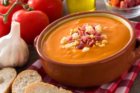 Typical Spanish salmorejo cream with ham and egg on wooden table