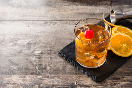 Old fashioned cocktail with orange and cherry on wooden table. Copyspace Reklamní fotografie