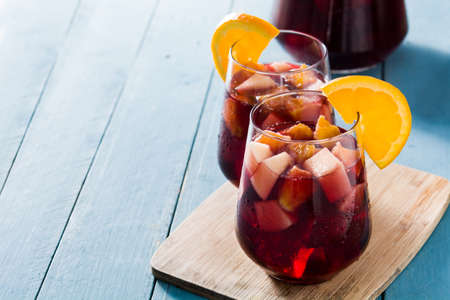 Red wine sangria in glass on blue wooden table. Copyspace Banco de Imagens