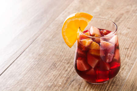 Red wine sangria in glass on wooden table. Copyspace
