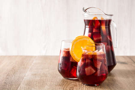 Red wine sangria in glasses on wooden table. Copyspace
