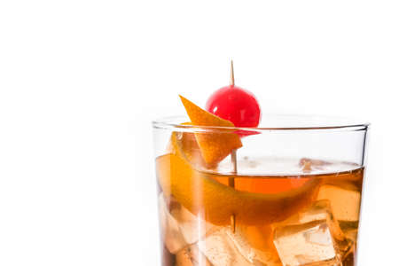 Old fashioned cocktail with orange and cherry isolated on white background. Copyspace