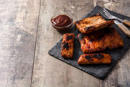 Grilled barbecue ribs on wooden table.