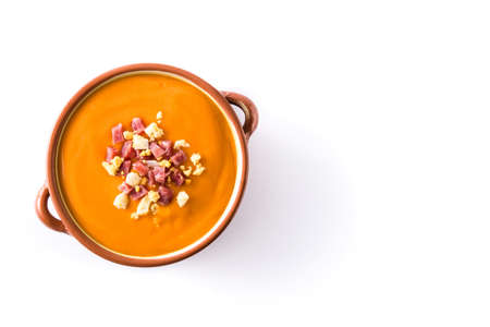 Typical Spanish salmorejo cream with ham and egg isolated on white background.