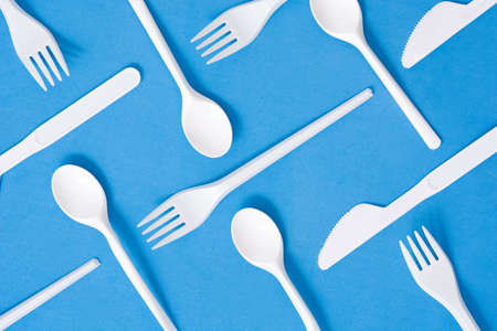 Disposable plastic tableware pattern on blue background Imagens