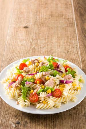 Ensalada de pasta con verduras y atún en mesa de madera. Foto de archivo