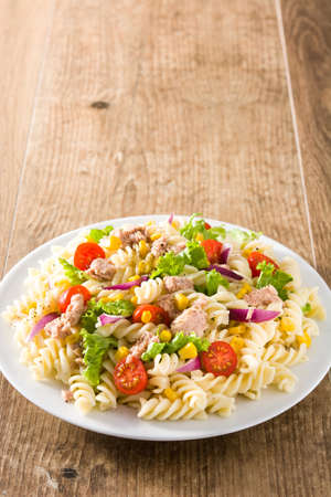 Pasta salad with vegetables and tuna on wooden table. Imagens