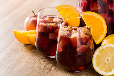 Red wine sangria in glasses on wooden table.
