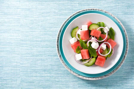 Watermelon salad with feta cheese,mint,onion and cucumber on blue background