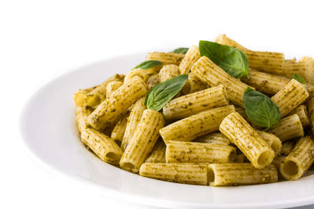 Penne pasta with pesto sauce and basil on a plate, isolated on white background 免版税图像