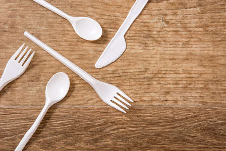 Disposable plastic cutlery on wooden table. Top view. Copyspace