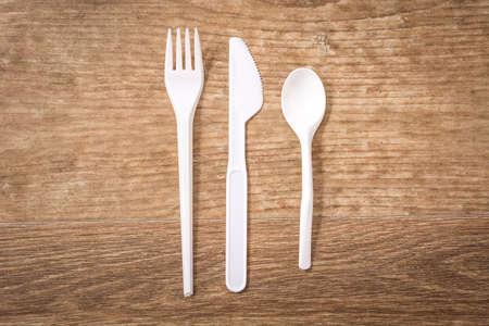 Disposable plastic cutlery on wooden table. Top view Imagens