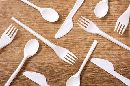 Disposable plastic cutlery on wooden table. Top view.