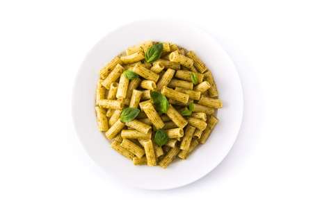 Penne pasta with pesto sauce and basil on a plate isolated on white background. Top view.