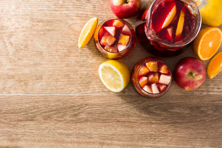 Red wine sangria in glasses on wooden table. Top view. Copyspace