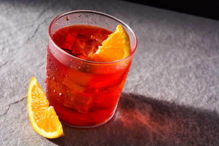 Negroni cocktail with piece of orange in glass on black background Banco de Imagens - 124669285