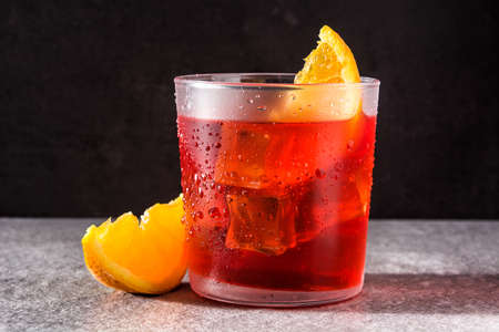 Negroni cocktail with piece of orange in glass on black background Banco de Imagens - 124669289