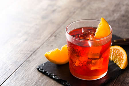 Negroni cocktail with piece of orange on wooden table Banco de Imagens
