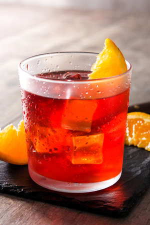 Negroni cocktail with piece of orange on wooden table Imagens