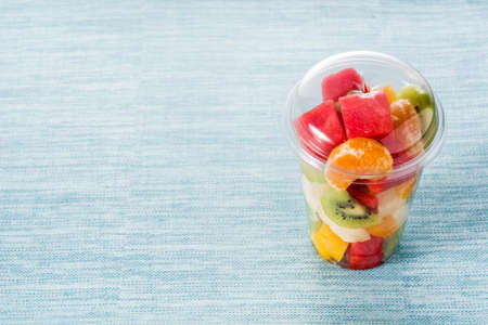 Fresh cut fruit in a plastic cup on blue background