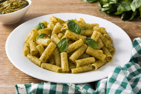 Penne pasta with pesto sauce on wooden table