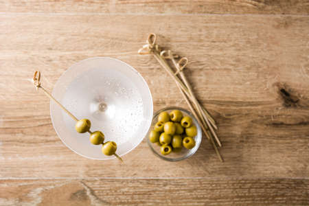Classic Dry Martini with olives on wooden table and gray background