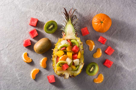Mix fruit served inside pineapple on gray background Imagens