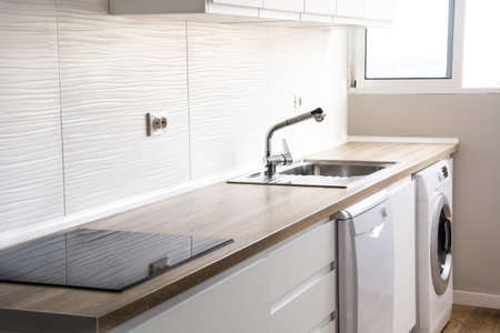 White modern kitchen with white furnitures and wooden floor