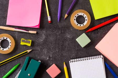 Materiale scolastico assortito su ardesia nera. Torna al concetto di scuola. Archivio Fotografico