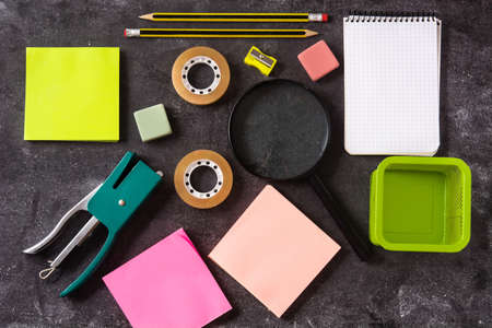 Assorted school supplies on black slate. Back to school concept.