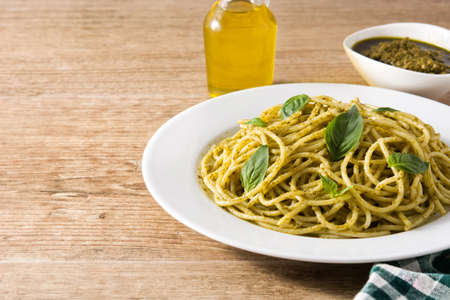Spaghetti pasta with pesto sauce on wooden table. Copyspace