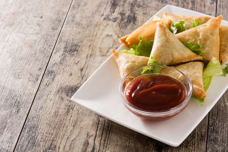 Samsa or samosas with meat and vegetables on wooden table. Traditional Indian food. Copyspace Stock Photo