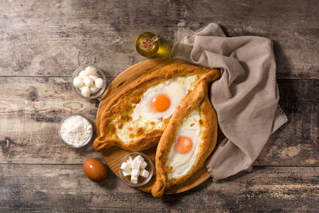 Traditional Adjarian Georgian khachapuri with cheese and egg on wooden table. Top view