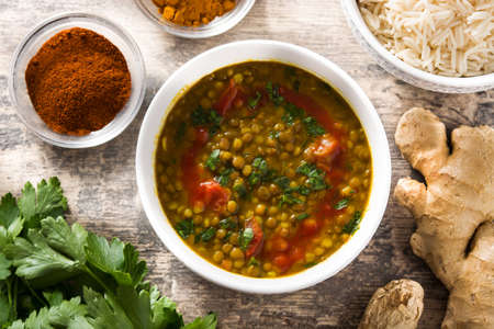 Indian lentil soup dal (dhal) in a bowl on wooden table. Top view