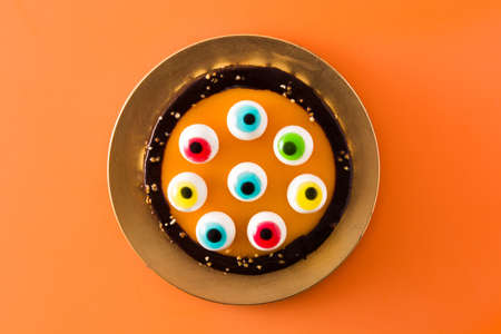 Halloween cake with candy eyes decoration on orange background.Top view.
