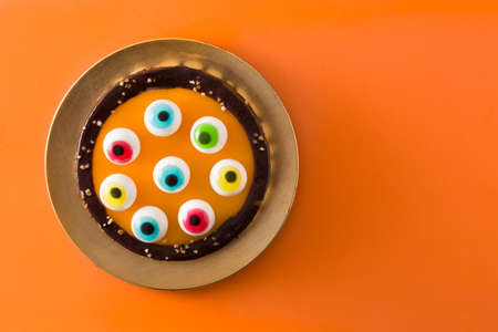 Halloween cake with candy eyes decoration on orange background.Top view. Copyspace Imagens