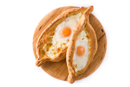 Traditional Adjarian Georgian khachapuri with cheese and egg isolated on white background. Top view. Imagens