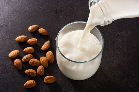 Pouring almond milk in glass on black background Imagens