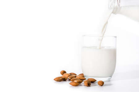 Pouring almond milk in glass isolated on white background. Copyspace Imagens