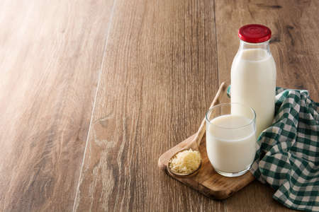Rice milk in glass and bottle on wooden table. Copyspace