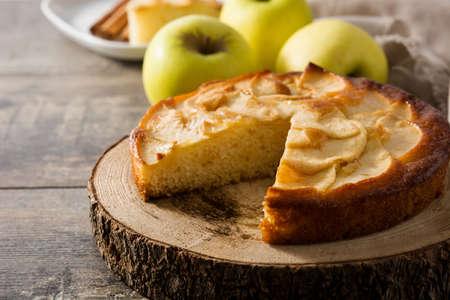 Homemade apple pie slice on wooden table. Imagens
