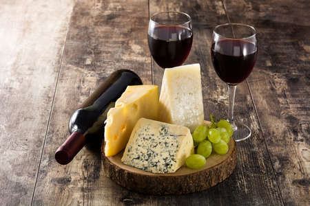Assortment of cheeses and wine on wooden table Imagens